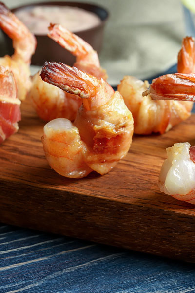 bacon-wrapped shrimp on a wooden serving tray